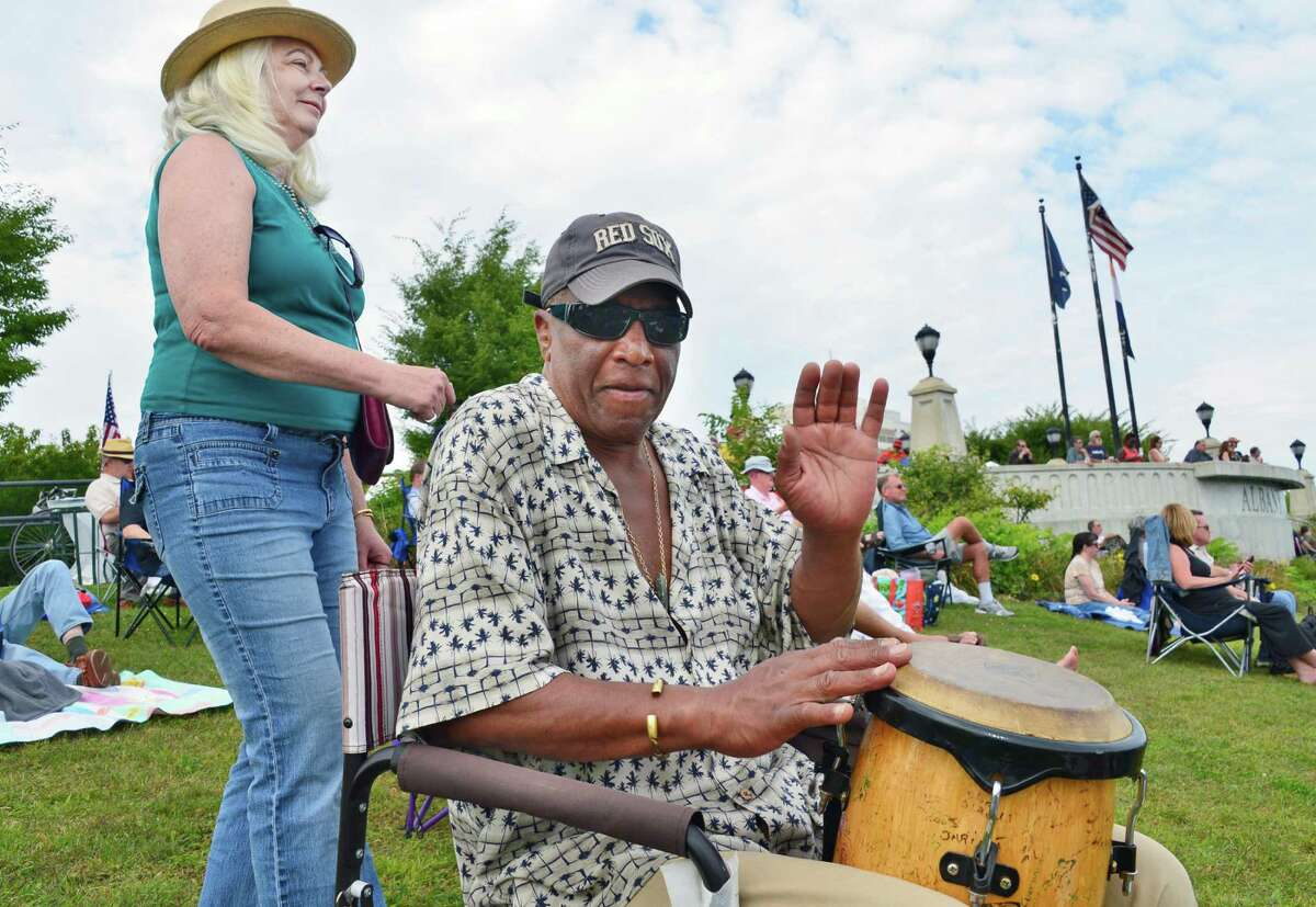 Peggy Zamierowski, left, dances as Jeffrey Bryan of Cape Cop plays his West African djimba drum in between bands at the Albany Riverfront Jazz Festival at the Corning Preserve Saturday, Sept. 7, 2013, in Albany, NY. (John Carl D'Annibale / Times Union)