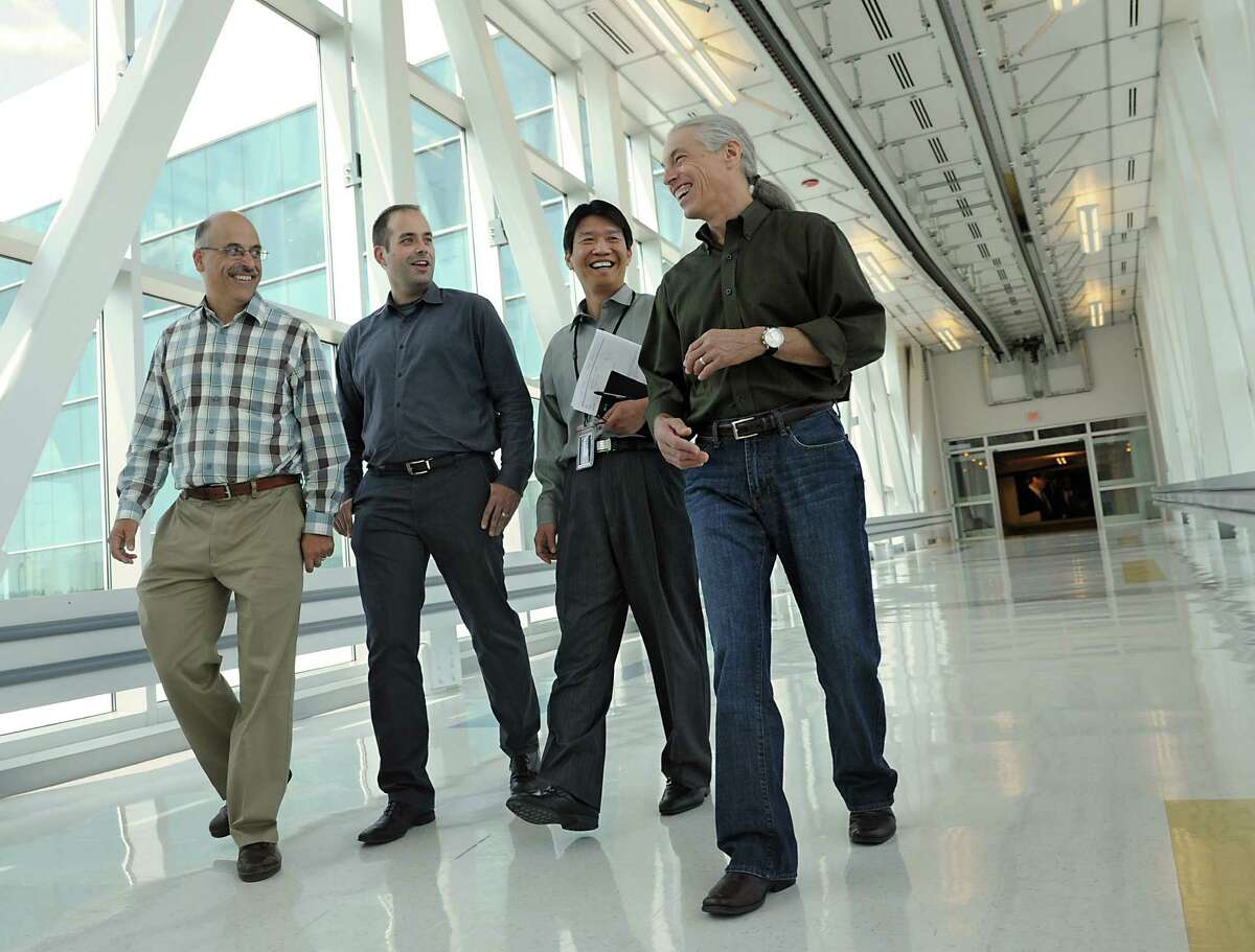 Global 450mm Consortium employees, Paul Farrar, general manager, left, David Skilbred, director of program director, John Lin, Ph.D., vice president and general manager and Frank Robertson, vice president and general manager, right, make their way down the walkway from the Nanofab X building at the College of Nanoscale Science and Engineering on Wednesday, Aug. 28, 2013, in Albany, N.Y. (Lori Van Buren / Times Union)