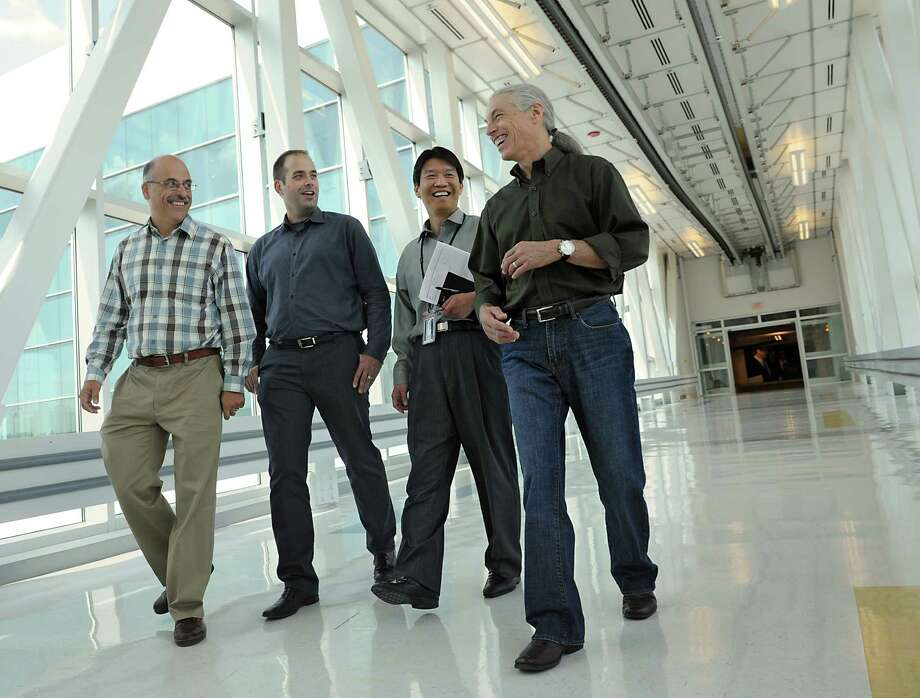 Global 450mm Consortium employees, Paul Farrar, general manager, left, David Skilbred, director of program director, John Lin, Ph.D., vice president and general manager and Frank Robertson, vice president and general manager, right, make their way down the walkway from the Nanofab X building at the College of Nanoscale Science and Engineering on Wednesday, Aug. 28, 2013, in Albany, N.Y.  (Lori Van Buren / Times Union) Photo: Lori Van Buren / 00023670A