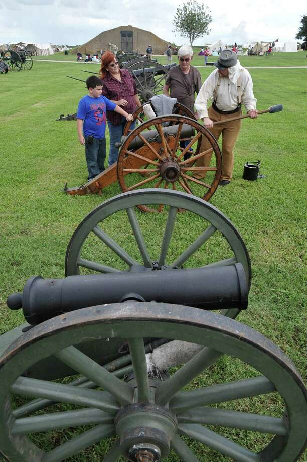 On the cannon line, Travis Hintzel, right, of Brahman Texas, gives a loading demonstration to a family. The annual Dick Dowling Days, hosted by the Texas Historical Commission, and held at the Sabine Pass historic battleground in Sabine Pass, saw some 300 plus re-enactors taking part this weekend in re-creating the Battle of Sabine Pass, which took place 150 years ago.  It is a two day event and the public is invited to walk through life as it was in1863, see period camps, history exhibits, witness battle reenactments with live canon fire, and cavalry charges. Dave Ryan/The Enterprise Photo: Dave Ryan