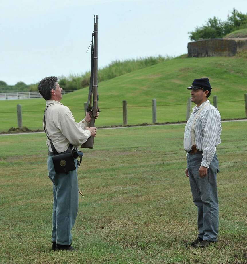 Jesse Rodriguez, of Beaumont, right, works with Rick Flanagan, left, of League City on the proper ways to march with a rifle. The annual Dick Dowling Days, hosted by the Texas Historical Commission, and held at the Sabine Pass historic battleground in Sabine Pass, saw some 300 plus re-enactors taking part this weekend in re-creating the Battle of Sabine Pass, which took place 150 years ago.  It is a two day event and the public is invited to walk through life as it was in1863, see period camps, history exhibits, witness battle reenactments with live canon fire, and cavalry charges. Dave Ryan/The Enterprise