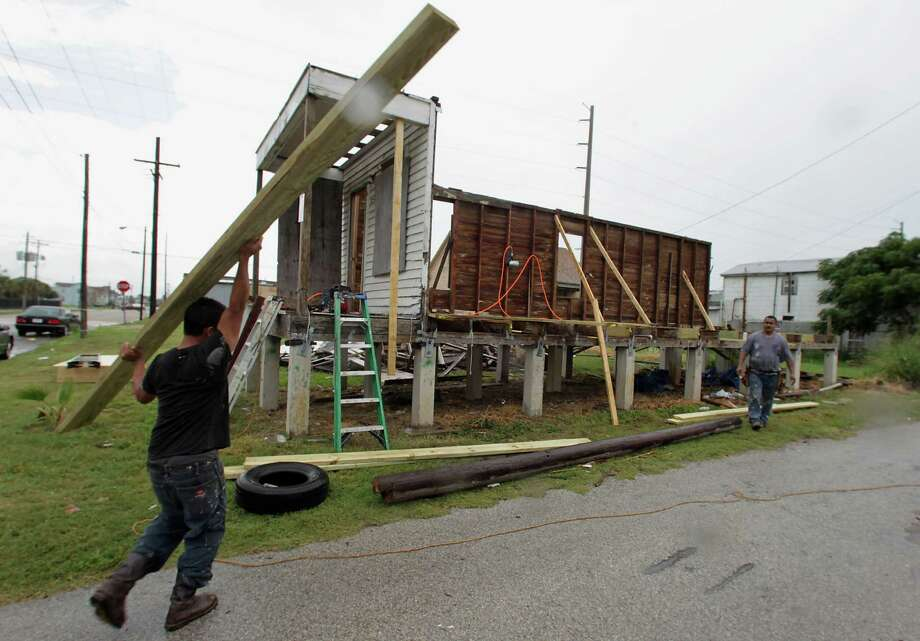 A crew with The Renovation Team Inc. works Wednesday to rebuild a home damaged by Hurricane Ike in the 600 block of Jack Johnson Boulevard in Galveston. Photo: James Nielsen, Staff / © 2013  Houston Chronicle