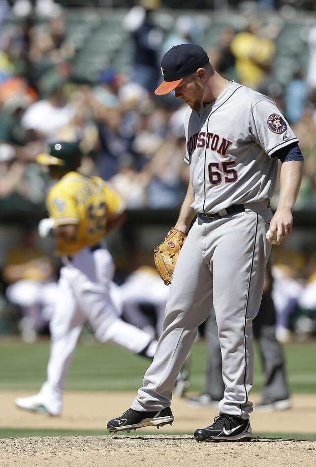 Astros pitcher Brett Oberholtzer reacts after giving up a home run to the A's. Photo: Jeff Chiu, Associated Press