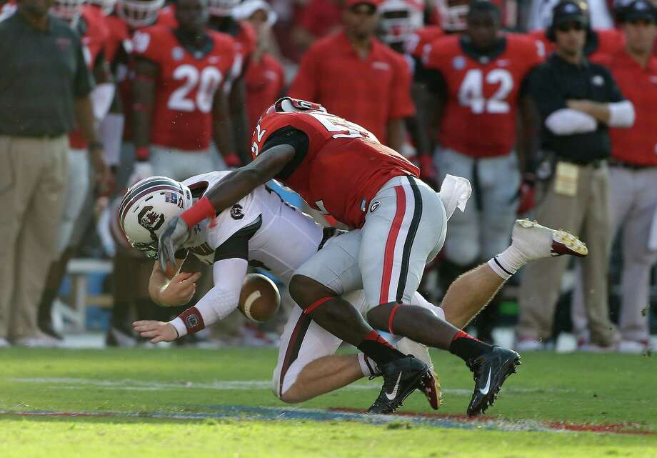 Georgia's Amarlo Herrera forces South Carolina quarterback Connor Shaw to fumble. Photo: John Bazemore, STF / AP