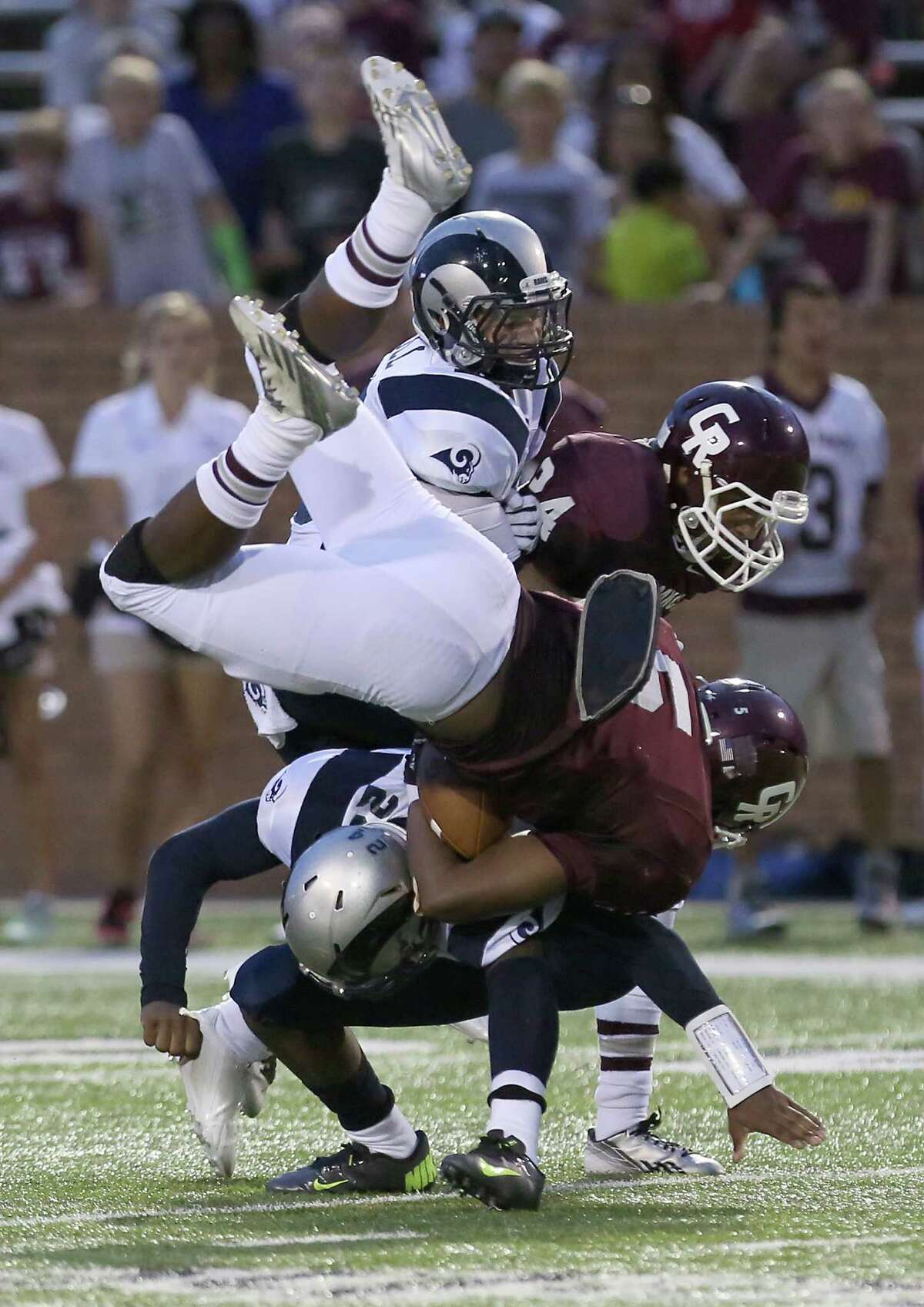 Cinco Ranch's Cougar Denzell Bates #5 flips as he is tackled by Cy Ridge Ram Cody Montgomery #22 at Rhodes Stadium in Katy, Texas.
