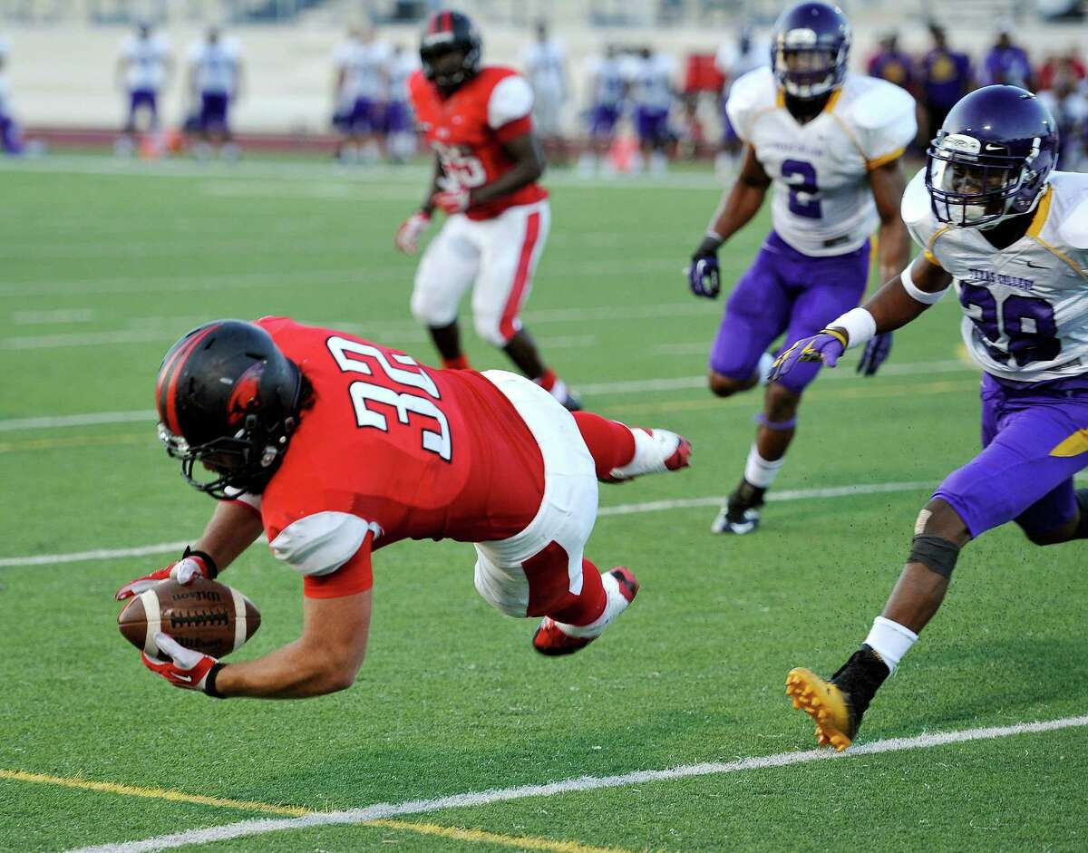 Incarnate Word full back Matt Bass (32) dives for a touchdown ahead of Texas College defensive back Devonte Volter, right, during the first half of a college football game, Saturday, Sept. 7, 2013, at the University of the Incarnate Word in San Antonio. (Darren Abate/For the Express-News)