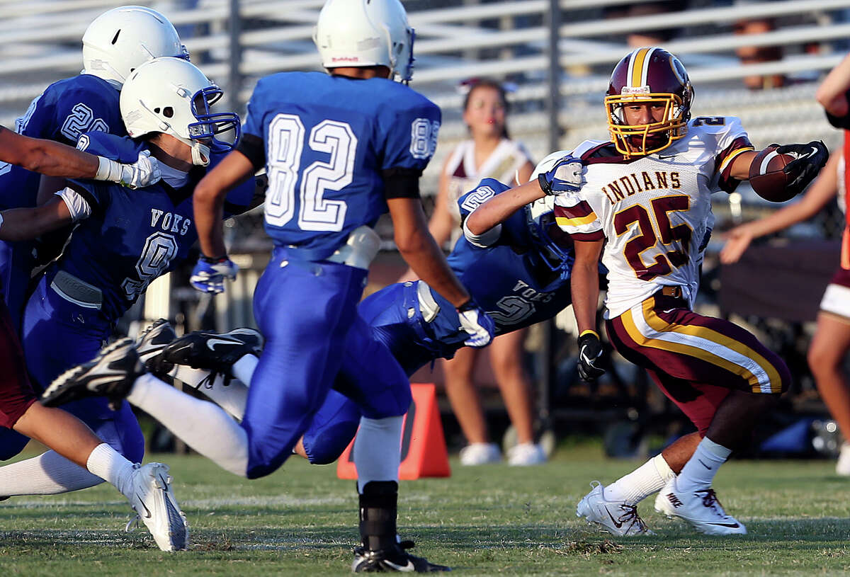 Indian running back John Aguirre gets through on the left as Lanier plays Harlandale at SAISD Spring Sports Complex on September 7, 2013.