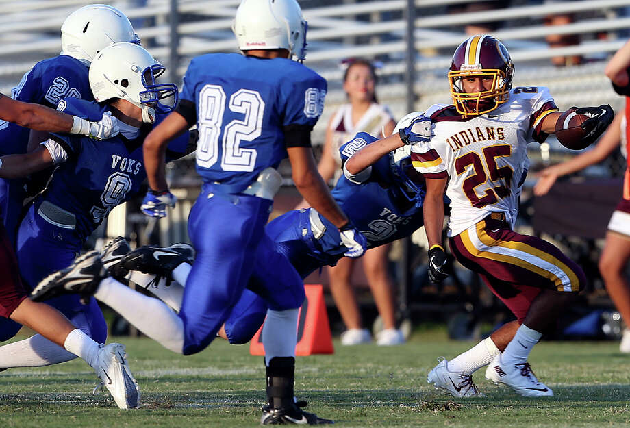 Indian running back John Aguirre gets through on the left as Lanier plays Harlandale at SAISD Spring Sports Complex on September 7,  2013. Photo: TOM REEL