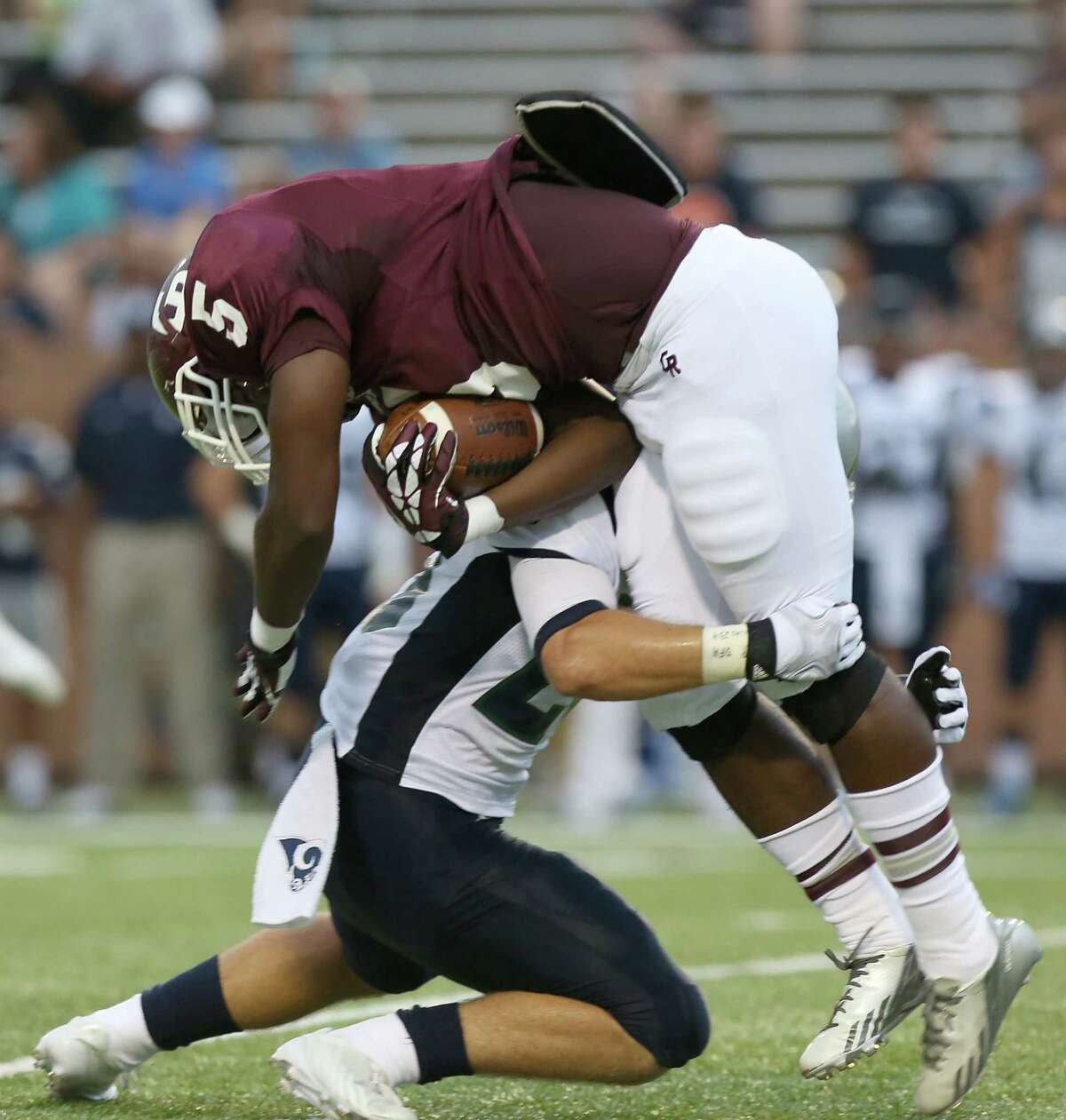 9/7/13: Cinco Ranch Cougar Denzell Bates #5 is tackled by Cy Ridge Ram Justin McBride #27 at Rhodes Stadium in Katy, Texas.