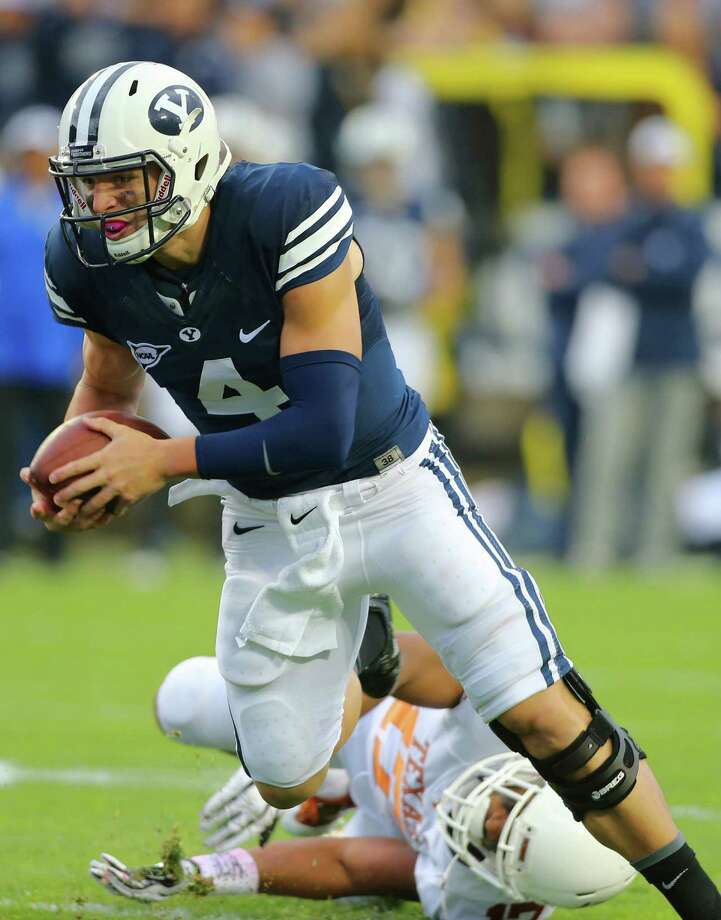 PROVO, UT - SEPTEMBER 7: Taysom Hill #4 of the BYU Cougars runs out of a tackle by Miles Onyegbule #17 of the Texas Longhorns during the first half of an NCAA football game on September 7, 2013 at LaVell Edwards Stadium in Provo, Utah. Photo: George Frey, Getty Images / 2013 Getty Images