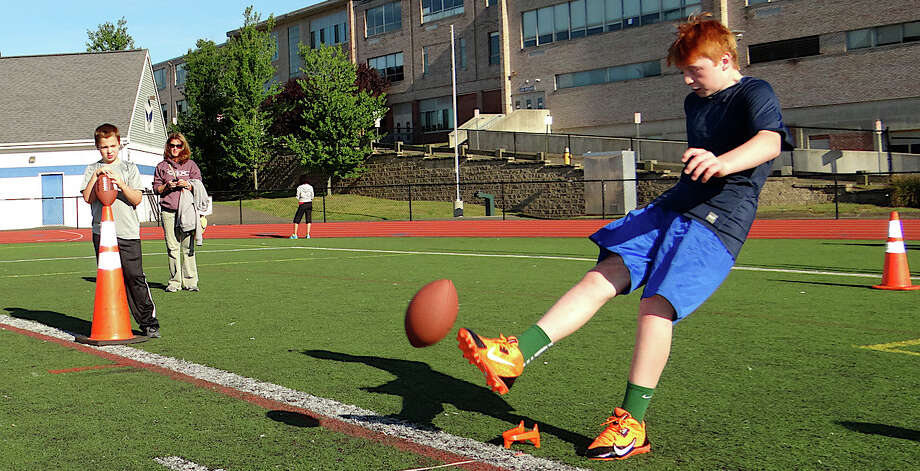 David Summers, 12, a quarterback for the Wildcats in the Fairfield Youth League, kicks a football at Fairfield Police Athletic League's Punt, Pass & Kick session Saturday morning. Photo: Mike Lauterborn / Fairfield Citizen contributed