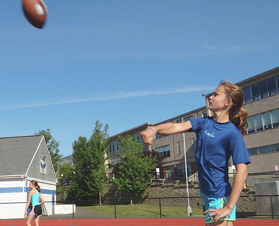 Jackie Soderlund, 10, a Roger Ludlowe Middle School student, tries her hand passing a football Saturday at the  Punt, Pass & Kick competition. Photo: Mike Lauterborn / Fairfield Citizen contributed