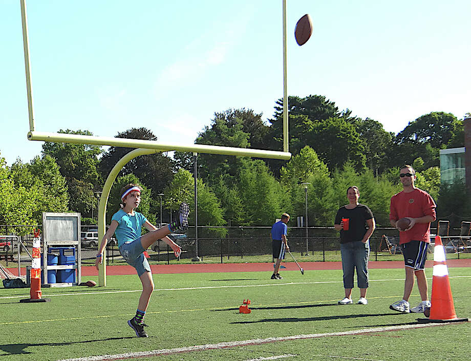 Kayleigh Gallagher, 8, a Roger Sherman Elementary School student, kicks during the Fairfield PAL Punt, Pass & Kick competition Saturday. Photo: Mike Lauterborn / Fairfield Citizen contributed