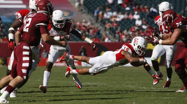UH defensive back Adrian McDonald dives forward after grabbing an interception against Temple. Photo: Johnny Hanson, Houston Chronicle