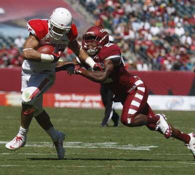 UH running back Kenneth Farrow tries to avoid a Temple defender. Photo: Johnny Hanson, Houston Chronicle