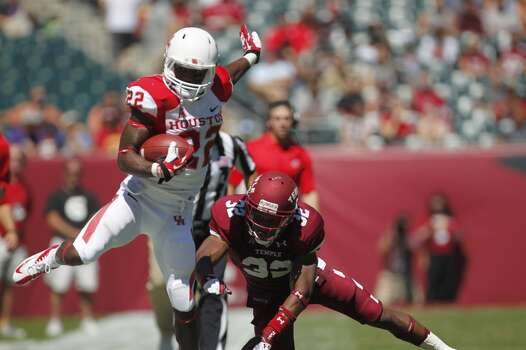 UH running back Ryan Jackson tries to elude a Temple defender. Photo: Johnny Hanson, Houston Chronicle