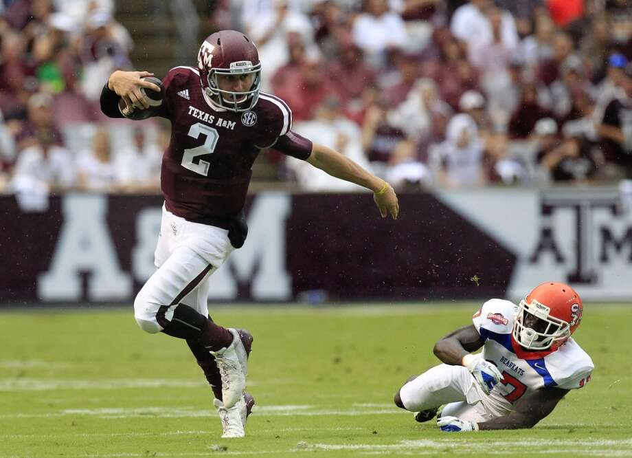 Texas A&M Aggies quarterback Johnny Manziel dodges a tacks from Sam Houston State Bearkats cornerback Bookie Sneed as he looks for running room. Photo: Cody Duty, Houston Chronicle