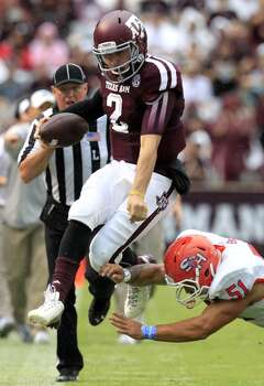 Texas A&M Aggies quarterback Johnny Manziel jumps as he's driven out of bounds from Sam Houston State Bearkats linebacker Eric Fieilo. Photo: Cody Duty, Houston Chronicle