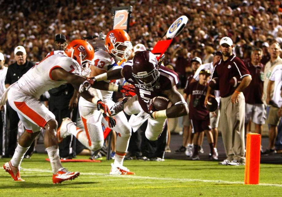 Texas A&M Aggies running back Brandon Williams dives past Sam Houston State Bearkats safety Johntel Franklin, left, and linebacker Jesse Beauchamp, center, for a touchdown. Photo: Cody Duty, Houston Chronicle