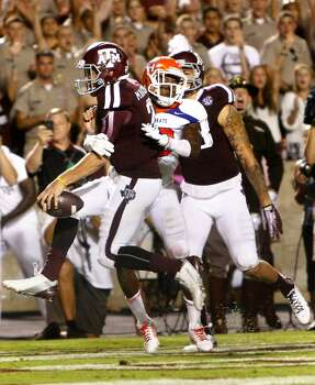 Sam Houston State Bearkats cornerback DeAntrey Loche comes up short on a tackle as Texas A&M Aggies quarterback Johnny Manziel  runs the ball in for a touchdown. Photo: Cody Duty, Houston Chronicle