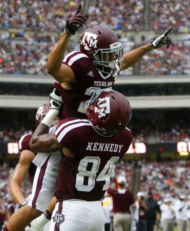 Texas A&M Aggies wide receiver Malcome Kennedy lifts wide receiver Sabian Holmes after he scored a touchdown. Photo: Cody Duty, Houston Chronicle