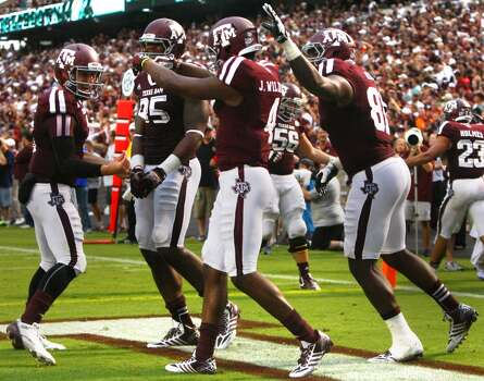 Texas A&M Aggies quarterback Johnny Manziel, left, gestures to wide receiver Ja'Quay Williams, center, after he caught a touchdown pass. Photo: Cody Duty, Houston Chronicle