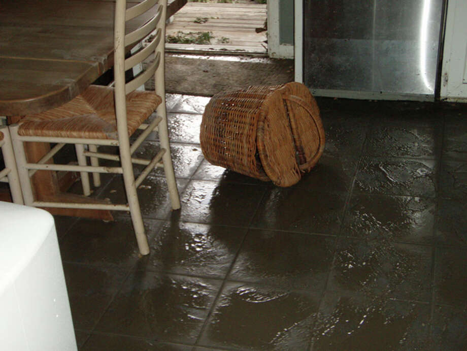 The Kitchen photo shows the mud that was left behind, and the watermark on the dishwasher.  My home was on pier and beam and about 3-1/2 feet above ground, but 14 inches of water flooded the house.  The door in the Back Deck photo is the same door you see in the kitchen photo. Photo: Karen Heck