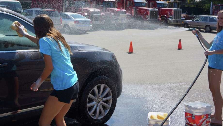Members of the Staples High School tackled a line of dirty cars Sunday during their annual car wash at Kowalsky Brothers. Photo: Todd Tracy / Westport News