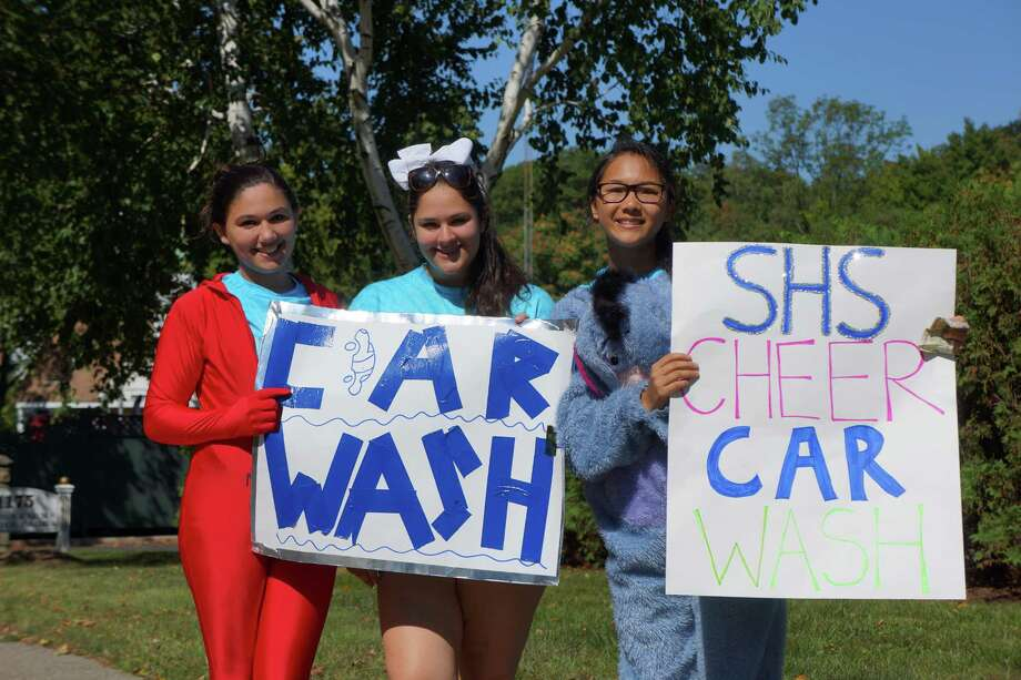 Members of Staples High School hail passing Post Road traffic for their annual car wash on Sunday morning. Photo: Todd Tracy / Westport News