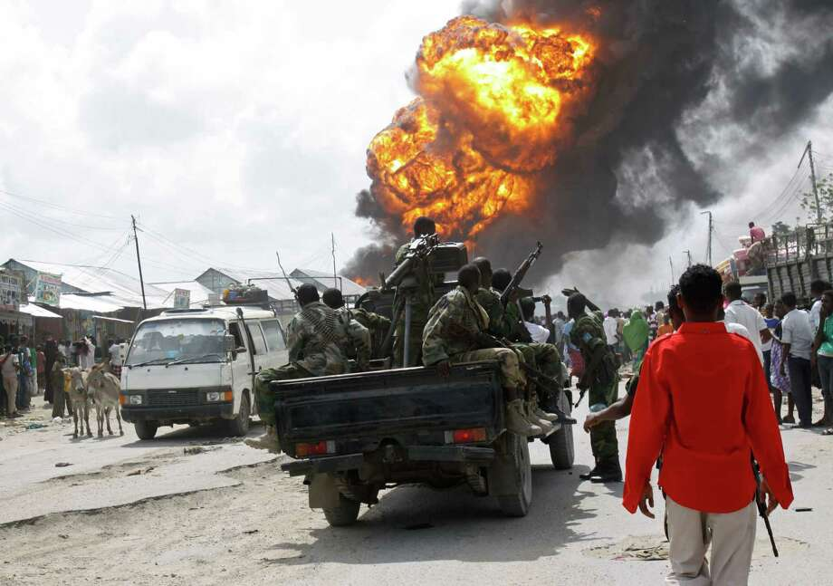 Somali soldiers on patrol pass a market fire in the capital Mogadishu, Somalia Tuesday, Sept. 3, 2013. The inferno largely destroyed the Seybiyano market in the west of the capital before it was put out by emergency services and local residents. Photo: AP