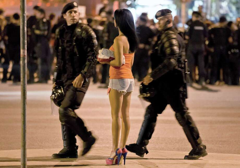 Romanian riot policeman prepare to confront protesters, as a woman views the scene and demonstrators gather nearby, in Bucharest, Romania, early Thursday, Sept. 5, 2013. Protesters blocked traffic in central Bucharest for the fourth day running to protest against the proposed development in the Transylvanian town of Rosia Montana, by Canadian mining company Gabriel Resources of Europe's largest cyanide based extraction open-cast gold mine. Photo: AP