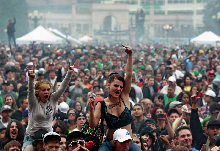 FILE - In this April 20, 2013 file photo, members of a crowd numbering tens of thousands smoke marijuana and listen to live music, at the Denver 420 pro-marijuana rally at Civic Center Park in Denver.  Medical marijuana businesses worried that federal agents will close them down now have a roadmap to avoid prosecution, courtesy of the Justice Department's decision to allow legal pot in Colorado and Washington state. Photo: AP
