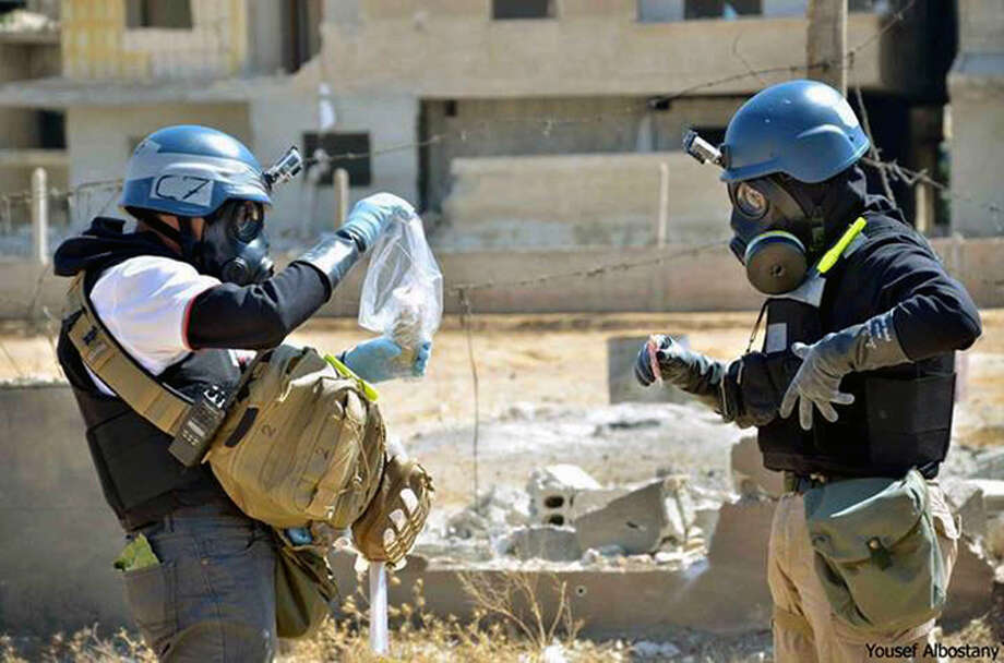 In this Aug. 28, 2013, citizen journalism image provided by the United Media Office of Arbeen which has been authenticated based on its contents and other AP reporting, members of the UN investigation team take samples from sand near a part of a missile that is likely to be one of the chemical rockets according to activists, in the Damascus countryside of Ain Terma, Syria. The U.S. government insists it has the intelligence to prove a connection between the government of President Bashar Assad to the alleged chemical weapons attack last month that killed hundreds of people in Syria_but in the absence of such evidence, Damascus and its ally Russia have aggressively pushed another scenario: that rebels carried out the Aug. 21 chemical attack. Photo: AP