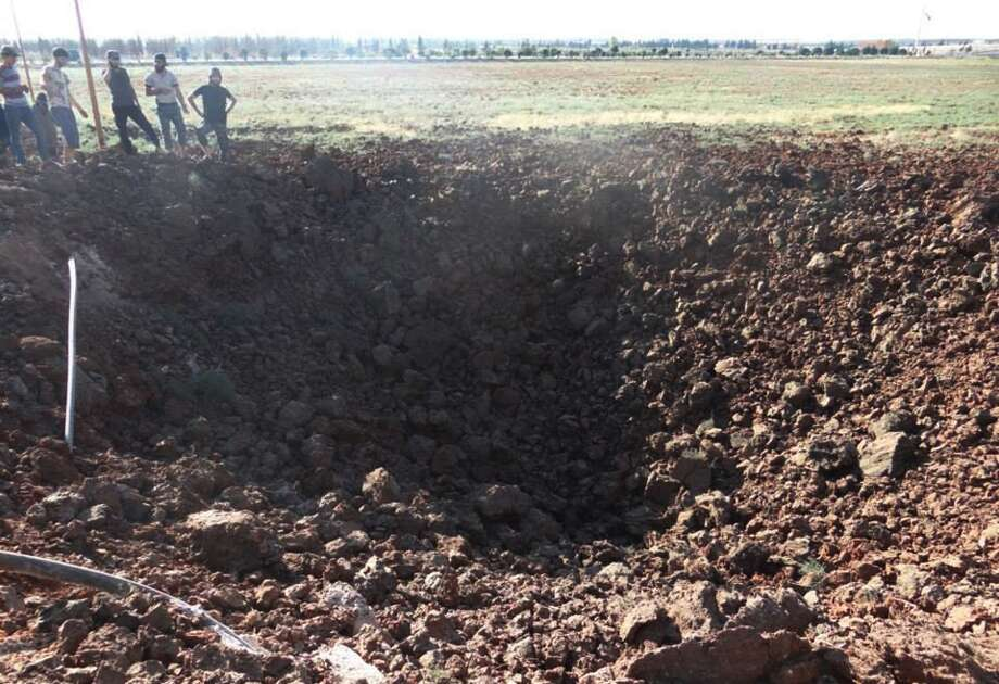 In this Wednesday, Sept. 4, 2013 citizen journalism image provided by Edlib News Network, ENN, which has been authenticated based on its contents and other AP reporting, Syrian men look at a crater caused by an air strike bomb that hit Sarakeb, Idlib province, Syria. Photo: AP