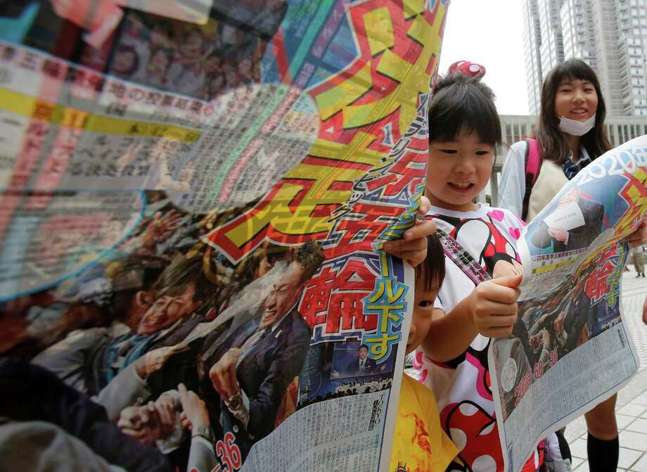 Japanese children get copies of a sports paper special edition printed to mark the International Olympic Committee's announcement of Tokyo as the host of the 2020 Summer Olympics Sunday morning, Sept. 8, 2013 in Tokyo. The IOC selected Tokyo, which hosted the 1964 Olympics, for the 2020 games in Buenos Aires, Argentina. The headline reads: 2020 Tokyo Olympics Decided. (AP Photo) Photo: AP