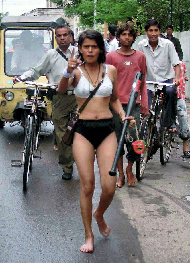 In this Wednesday, July 4, 2007 file photo, Indian woman Pooja Chauhan, in her undergarments and carrying a baseball bat and bangles in her hands, marches to the police commissioner's office to protest dowry harassment by her husband and in-laws, in Rajkot in the western Indian state of Gujarat. An Indian report released in August 2013, says a woman dies every hour in disputes over how much her family has paid in dowry to the groom for her marriage. The National Crime Records Bureau says more than 8,200 women were killed across India in such crimes last year even though Indian law prohibits the centuries-old custom of giving or receiving dowries. Photo: AP