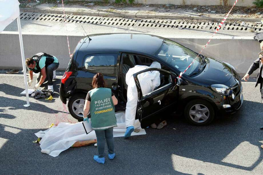 Policemen and judiciaries experts investigate in a crime scene  in Marseille, southern France, Thursday, Sept. 5, 2013. The victim who was killed by men with motorcycle, while he drove his car, is Adrien Anigo, son of Jose Anigo, Sports Director of  Olympique Marseille soccer club. Photo: AP