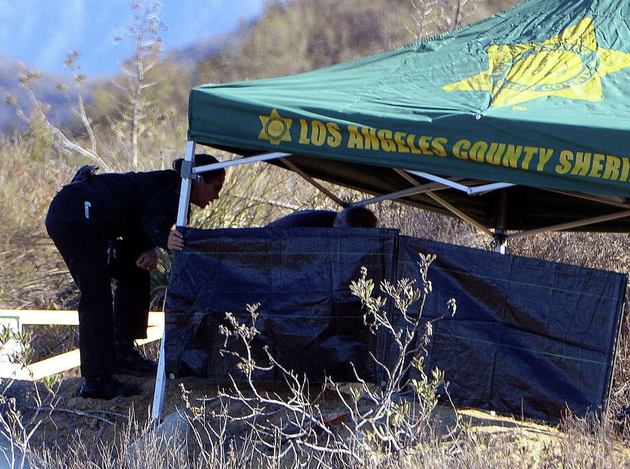 Bomb technicians search for arson evidence by a Sheriff's Department shade tent that covers a burned body found on the side of Lake Hughes Road a few miles above the Castaic Lake, Calif., on Wednesday, Sept. 4, 2013.   A burning body was found a Southern California lake where authorities had been searching for a college student who vanished a week ago but his family urged well-wishers to keep hoping that 19-year-old Bryce Laspisa would turn up alive.  Firefighters called to the scene of a small brush blaze near Castaic Lake at around 6 a.m. discovered the body, sheriff's Capt. Mike Parker told City News Service.  The body was too badly burned to immediately determine its sex or identity, authorities said. Photo: AP