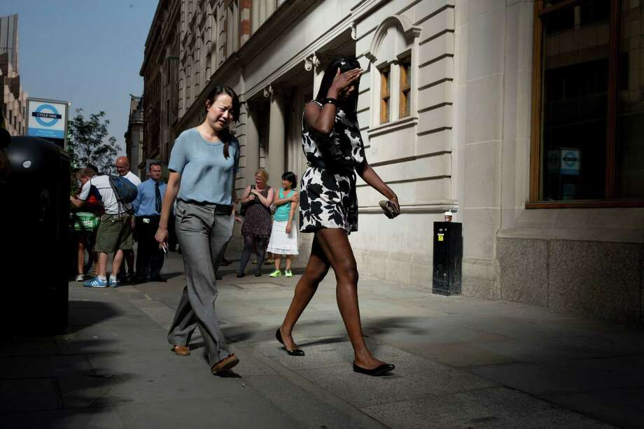 Women react as they walk through the intense sunlight reflecting down on them from the 37-storey skyscraper at 20 Fenchurch Street in the City of London, Thursday, Sept. 5, 2013.  Motorists may want to think twice about parking in front of the half-built London skyscraper known as the Walkie-Talkie.  That's because the glare off the skin of the new building is so intense that at least one Jaguar owner says it caused part of his vehicle to melt.  The problem lasts about two hours a day and is expected to continue for another two to three weeks because of the current elevation of the sun in the sky. Photo: AP