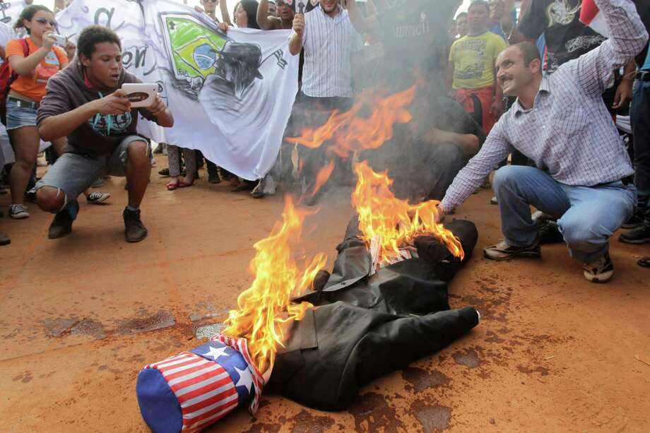 An effigy representing President Barack Obama burns on the ground during a protest organized by the National Union of Students outside the U.S. embassy in Brasilia, Brazil, Friday, Sept. 6, 2013. Students are protesting possible U.S. military action against Syria. Photo: AP
