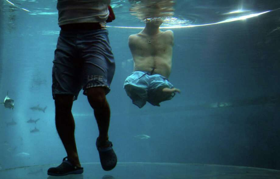 "Nick Vujicic, right, is accompanied by a life guard as he treads water in an acrylic enclosure keeping safe while diving among sharks, Thursday, Sept. 5, 2013 in Singapore. Vujicic, a Serbian Australian evangelist and motivational speaker born with tetra-amelia syndrome, a rare disorder characterized by the absence of all four limbs, is in the city-state to give a motivational talk and was visiting ""The Shark Encounter at Marine Life Park"" at one of Singapore's main tourist attractions in Resorts World Sentosa. Photo: AP"