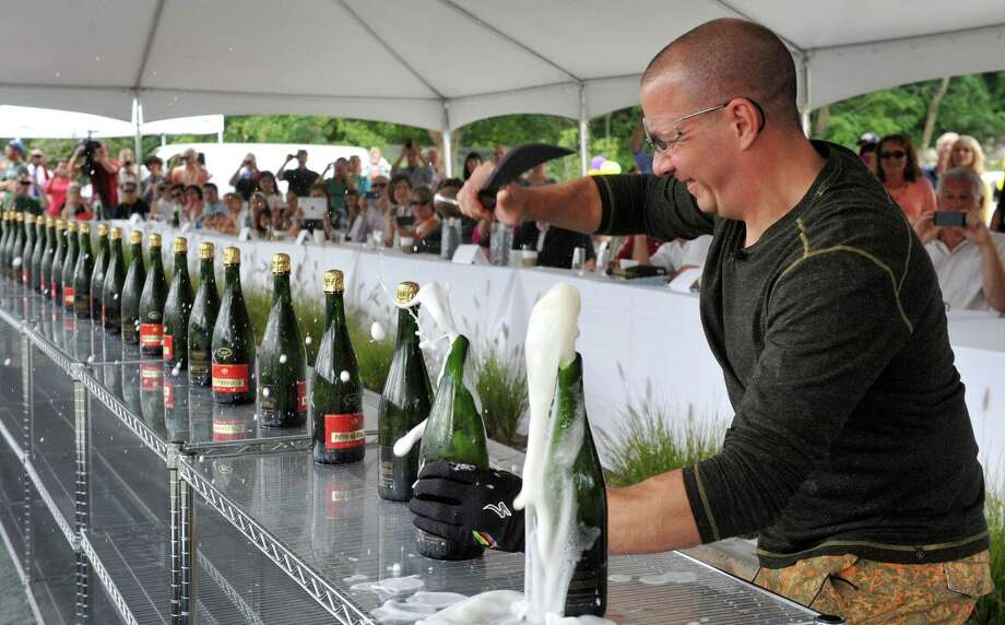 """Mitch Ancona beats the world record by opening 35 bottles of champange in one minute with a sabre during an event called """"One for the Books,"""" in Ridgefield, Conn. Sunday, Sept. 8, 2013. Proceeds from the event will be donated to the Ridgefield Library. The Guinness World Record had been 32 bottles in one minute. Photo: Michael Duffy / The News-Times"""