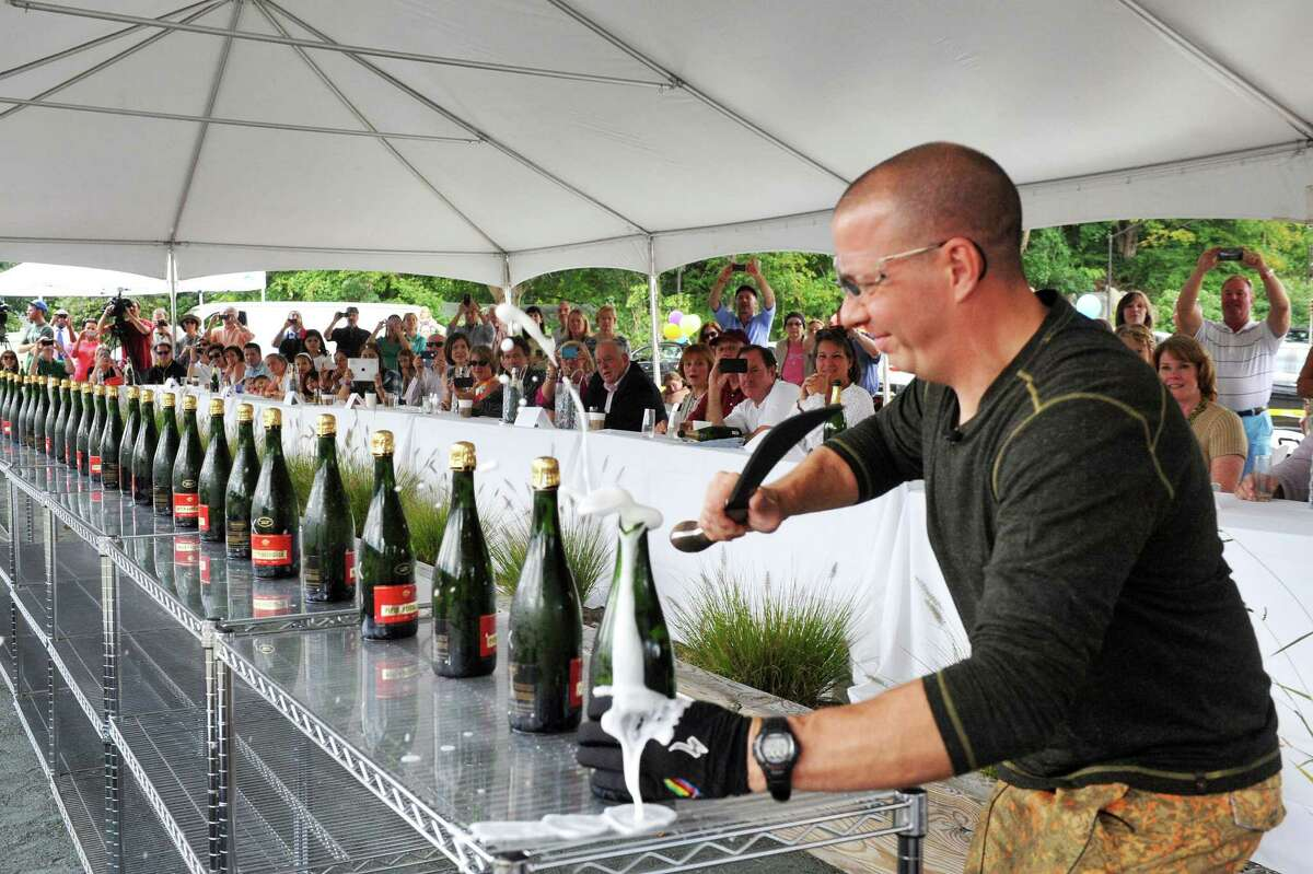 Mitch Ancona beats the world record by opening 35 bottles of champange in one minute with a sabre during an event called