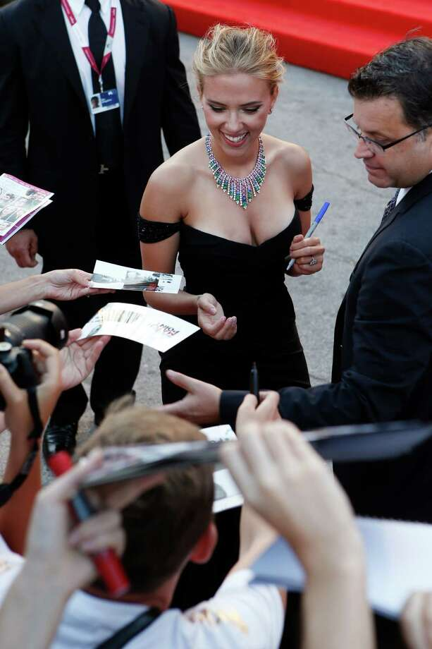 Actress Scarlett Johansson signs autographs for members of the public as she arrives on the red carpet for the screening of the film Under The Skin at the 70th edition of the Venice Film Festival held from Aug. 28 through Sept. 7, in Venice, Italy, Tuesday, Sept. 3, 2013. Photo: AP