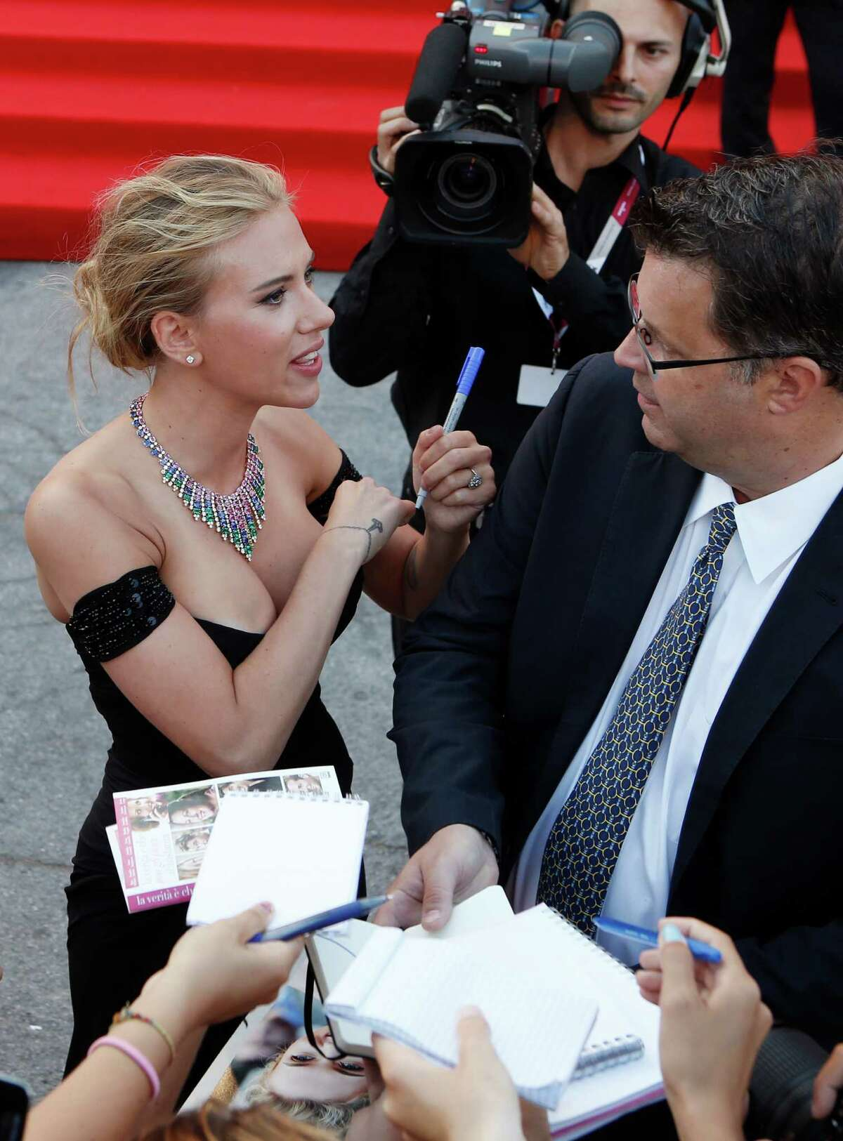 Actress Scarlett Johansson adjusts her dress as she signs autographs for members of the public as she arrives on the red carpet for the screening of the film Under The Skin at the 70th edition of the Venice Film Festival held from Aug. 28 through Sept. 7, in Venice, Italy, Tuesday, Sept. 3, 2013.