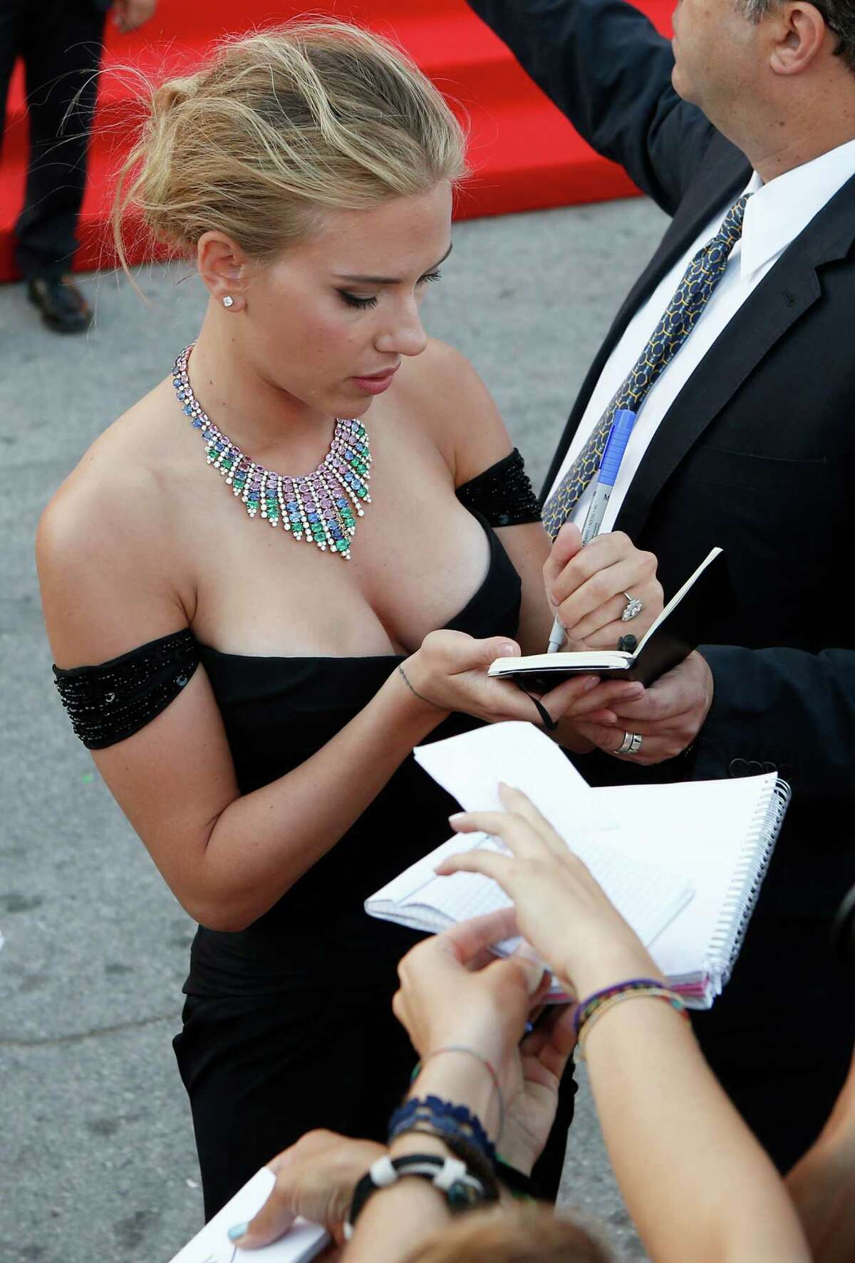 Actress Scarlett Johansson signs autographs for members of the public as she arrives on the red carpet for the screening of the film Under The Skin at the 70th edition of the Venice Film Festival held from Aug. 28 through Sept. 7, in Venice, Italy, Tuesday, Sept. 3, 2013.