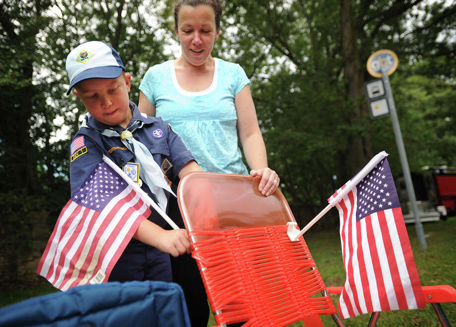 Cub scout Eddie Balog, 8, and his mom, Sue, of Shelton, add flags to their chairs as they await the arrival of the 13th annual CT United Ride on Park Avenue in Fairfield, Conn. on Sunday, September 8, 2013. The event is the largest single charity ride in New England as well as the largest 9/11 tribute in the State of Connecticut. Photo: Brian A. Pounds / Connecticut Post
