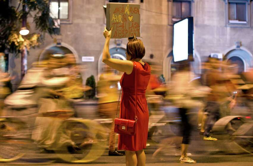 Protesters march past a woman holding a banner that reads