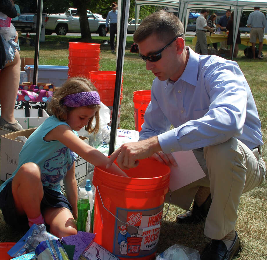Jim Muir of Norwalk and daughter Abby, 8, help put together buckets for emergency relief, part of Saugatuck Congregational Church's Hands-On Service project Sunday during a program to mark the start of reconstruction at the church. Photo: Jarret Liotta / Westport News contributed