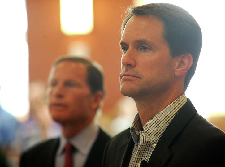 Rep. Jim Himes, right, and Sen. Richard Blumenthal listen to statements and questions from a packed